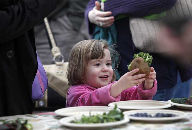 by: TIMES PHOTO: JONATHAN HOUSE - Savanah Montes smiles as she finishes her Mr. Potatohead, made with real vegetables, at a St. Patrick's Day-themed Beaverton Farmers Market on Saturday.