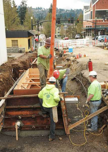 by: VERN UYETAKE - Crews pour concrete during construction work Monday on Second Street between A and B avenues downtown. Concrete will form the shells for eight stormwater-filtering planters, part of improvements the city is making on the street.