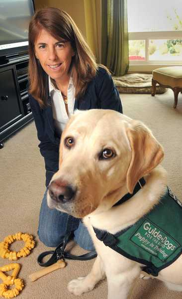 by: TIDINGS PHOTO: VERN UYETAKE - Shown with puppy-in-training Broadway, West Linn's Cindy Sullivan helps train guide dogs for the blind.