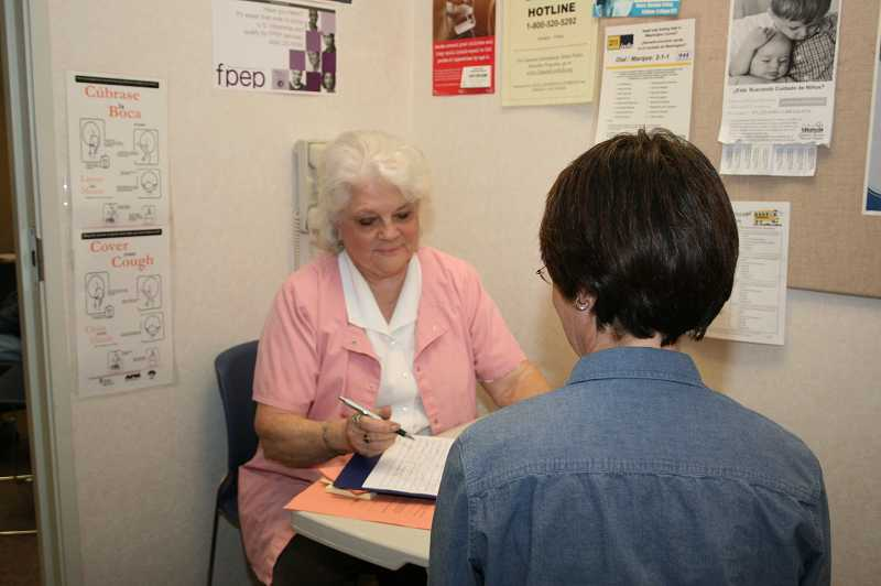 by: FILE PHOTO - Nurse Chris Foster consults with a patient at Essential Health Clinic in Tigard in 2010. The clinic closed its doors last week citing lack of funds