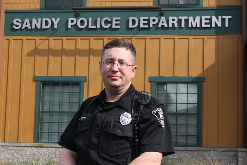 by: POST PHOTO: JIM HART - Sandy Police Officer Kevin Moody stands outside the Sandy Police Station, dressed in his patrol uniform, which he wears when he acts as a volunteer reserve officer. This year he is the Gresham Elks Officer of the Year for Sandy.