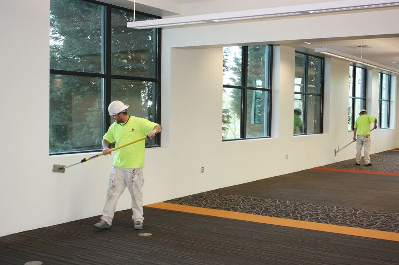 by: HILLSBORO TRIBUNE PHOTO: DOUG BURKHARDT - Contractors finish off one of the interior walls as work on the second floor of Hillsboro's main library nears completion.