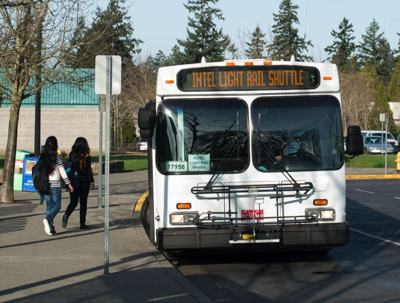 by: TRIBUNE PHOTO: DOUG BURKHARDT - An Intel shuttle bus picks up employees at the Orenco Station Max stop. TriMet is calling for additional shuttles between transit stops and work sites in its Westside Service Enhancement Plan.