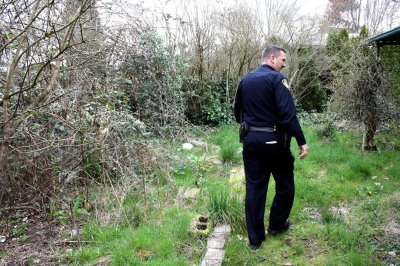 by: SPOTLIGHT PHOTO: KATIE WILSON - Scappoose Police Chief Doug Greisen walks through the overgrown backyard of a vacant home in Scappoose. Police have secured the entrances, but hope the new ordinances will hold property owners accountable for keeping the premises clean and safe.