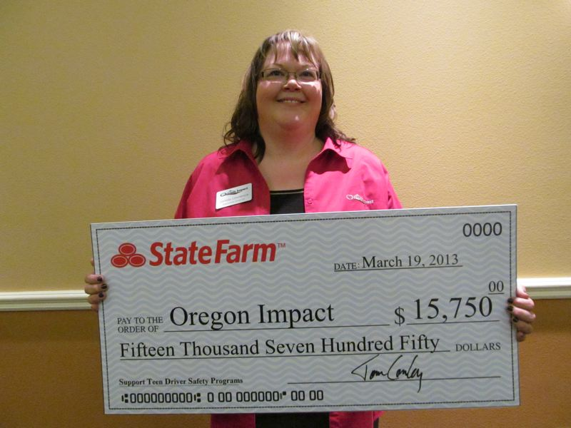 by: PHOTO BY: ELLEN SPITALERI - Janelle Meredith, executive director of Oregon Impact, Meredith accepts a check from State Farm Insurance.