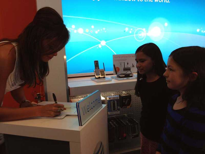 by: LORI HALL - Aubrey Cleland signs photos of herself for two young fans Monday at the AT&T store in Washington Square.