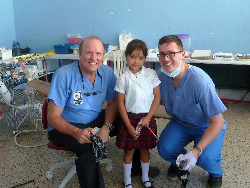 by: SUBMITTED PHOTO - David Streiff, left, and his assistant Mitchell Wilson brought a big smile to the face of this little Guatemalan girl.