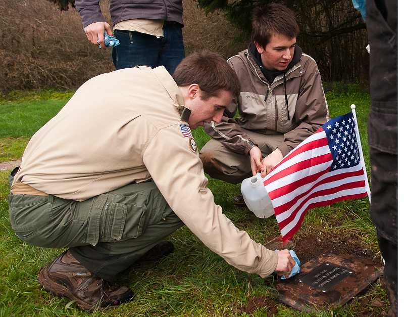 by: JOSH KULLA - Reed Burress cleans off one of the 12 grave markers he recently put in place to honor American veterans at the Pleasant View Cemetery outside Wilsonville.