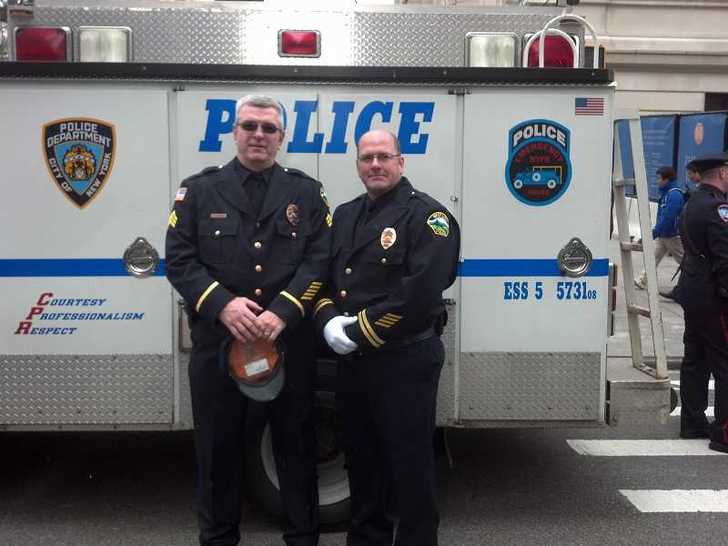 by: SUBMITTED PHOTO - Sgt. Neil Hennelly, left, and Officer Mike Francis stand in front of a police vehicle from Staton Island, where Hennelly grew up.