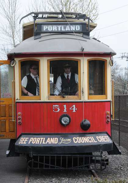 by: VERN UYETAKE - Gage Geist stands at the controls of the new Willamette Shore Trolley car in Lake Oswego on Tuesday while Itamar Reuven looks on.