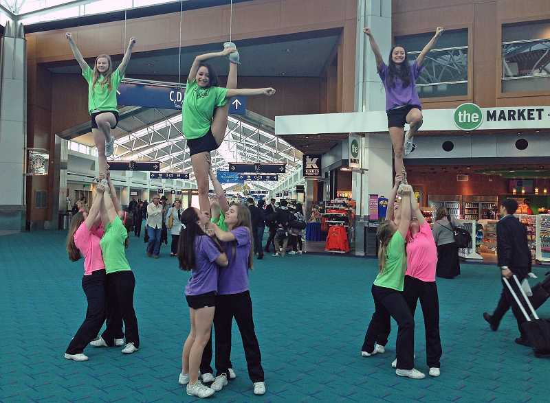 by: SUBMITTED PHOTO: CHRISTINE COOPER - Lakeridge High School cheer team members perform a few big stunts at the Portland International Airport on the way to the USA competition.