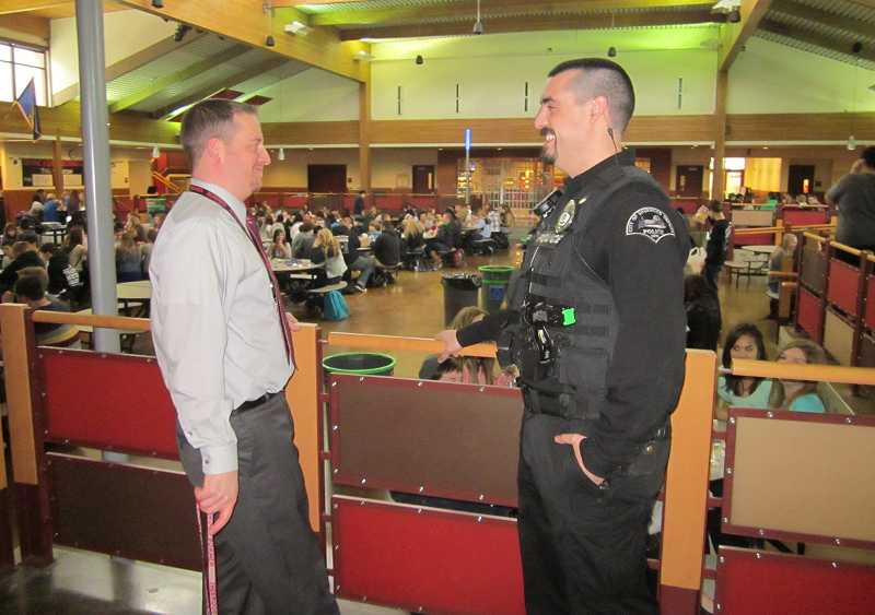 by: BARBARA SHERMAN - NOW ON DUTY - Sherwood School District school resource officer Kris Asla chats with Brian Bailey, Sherwood High School associate principal, in the SHS Commons during lunchtime.