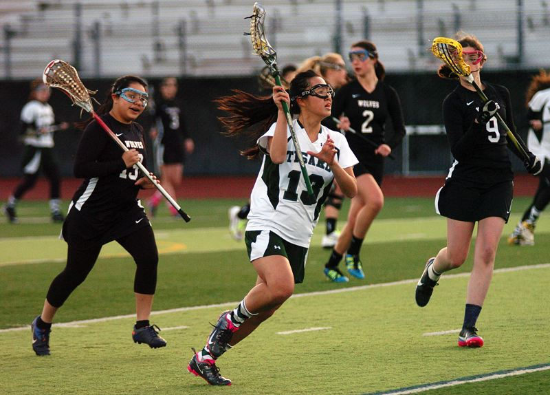 by: DAN BROOD - ON THE MOVE -- Tigard's Emily Nguyen (13) looks to drive up field against Tualatin's Jaila Godinez (left) and Haley Firth during Friday's game.