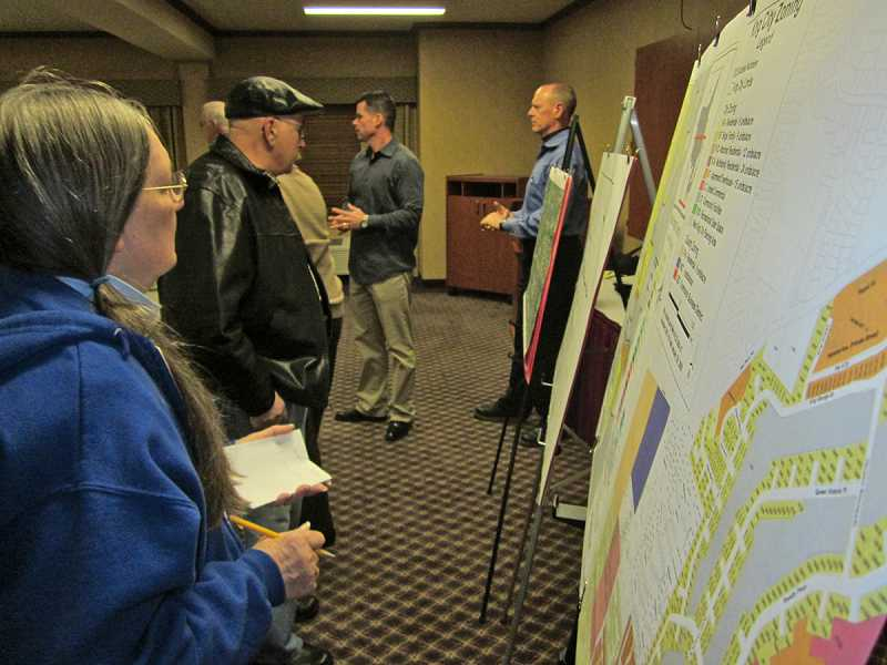 by: BARBARA SHERMAN - LOOKING AT THE FUTURE - People attending the Feb. 26 meeting at the Best Western Northwind Inn check out plans for a subdivision being proposed by Timberland Homes owner Steve Brown (center) on nearly 5 acres just south of the Highlands.