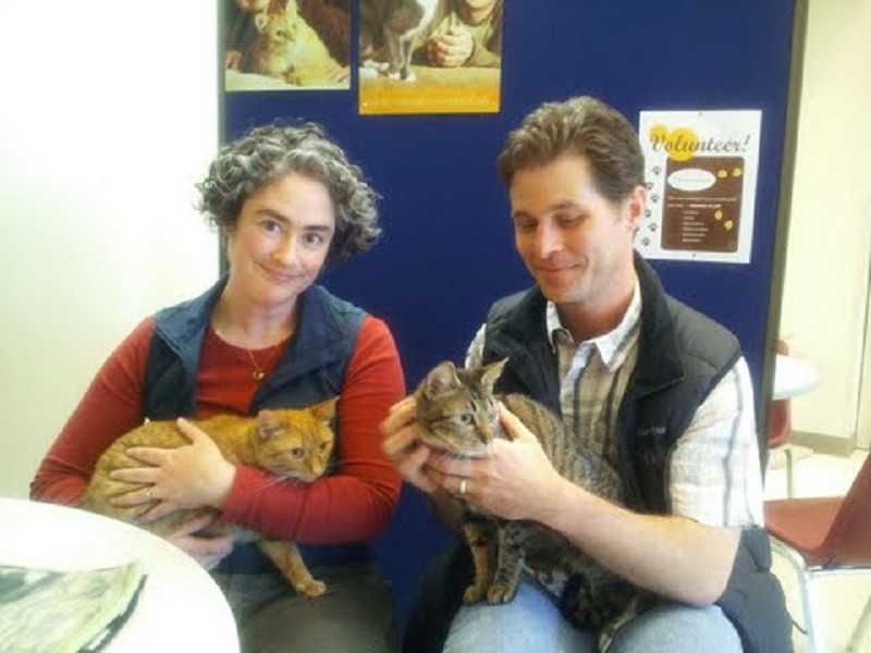 by: COURTESY OF CAT ADOPTION TEAM  - Melissa and Brett of Portland hold Grace, left, and Hazel, the two cats disovered in a sealed container and thrown in a trash container on March 23.