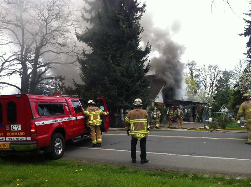 by: JAIME VALDEZ - Tualatin Valley Fire & Rescue crews survey the scene of a fire on Southwest Tigard Street, Monday afternoon.
