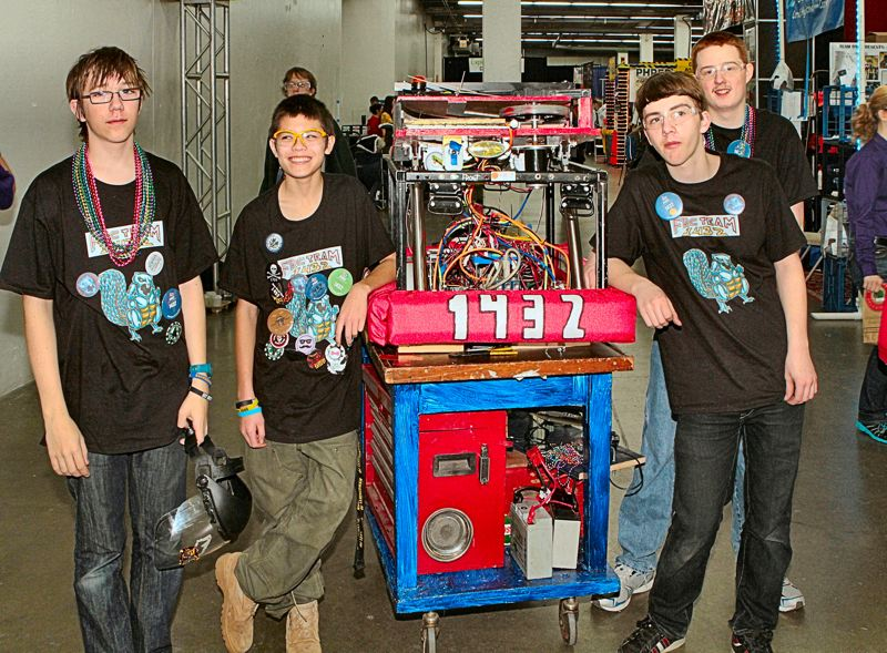 by: DAVID F. ASHTON - Some of the crew of FRC Team 1432 'Mahr's Metal Beavers' - Lewis Hicks, Mathew Robinett, Thomas Hubel, and Chase Foreman - wheel their robot back to their pit area after a competition.