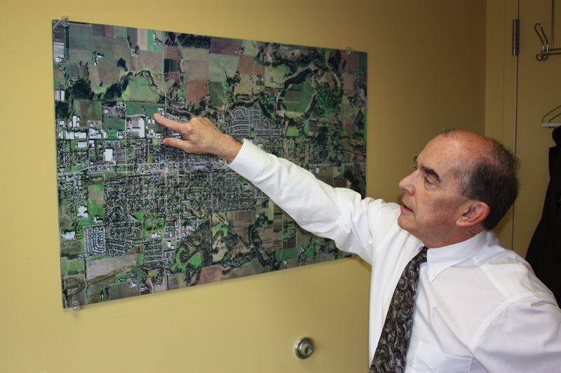 by: NEWS-TIMES PHOTO: DOUG BURKHARDT - Cornelius City Manager Rob Drake keeps a satellite map of the city he runs on the wall of his City Hall office.