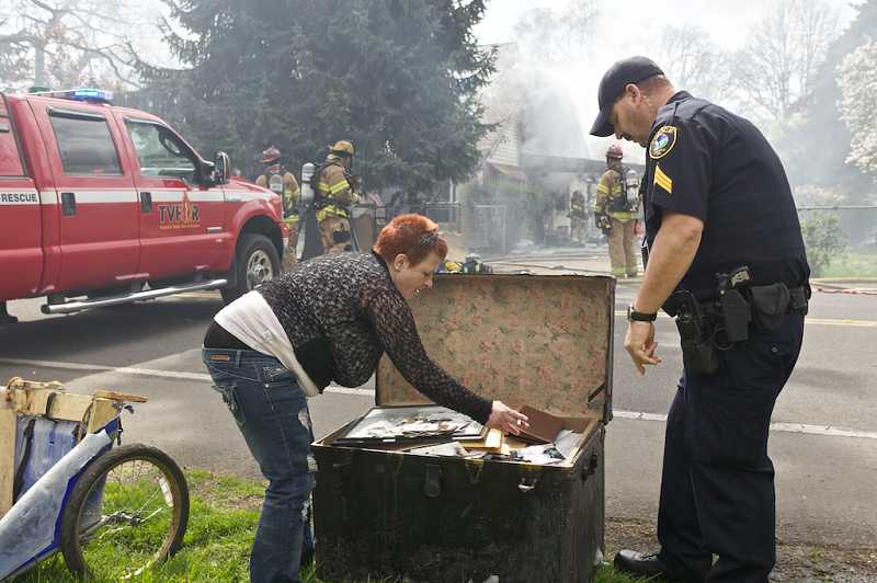by: TIMES PHOTO: JAIME VALDEZ - Darlene Malone looks through a trunk full of pictures and other memoirs saved from a fire in her home on Southwest Tigard Street.
