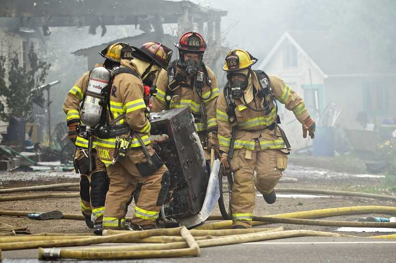 by: TIMES PHOTO: JAIME VALDEZ - Firefighters from Tualatin Valley Fire & Rescue haul a trunk from the wreckage of a burning home in Tigard. The trunk contained photos and other memorabilia that survived the fire.