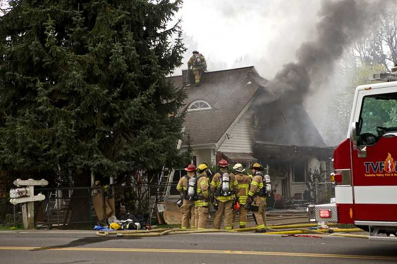 by: TIMES PHOTO: JAIME VALDEZ - Firefighters from Tualatin Valley Fire & Rescue respond to a house fire along Southwest Tigard Street in Tigard.