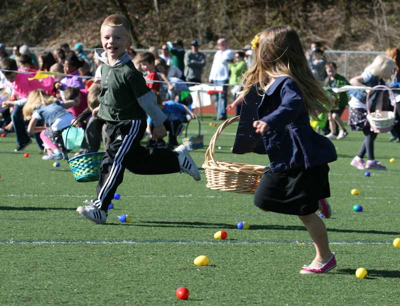 by: J. BRIAN MONIHAN - It's a mad dash to gather eggs filled with candy and prizes at the hunt at the West Linn High School football field.