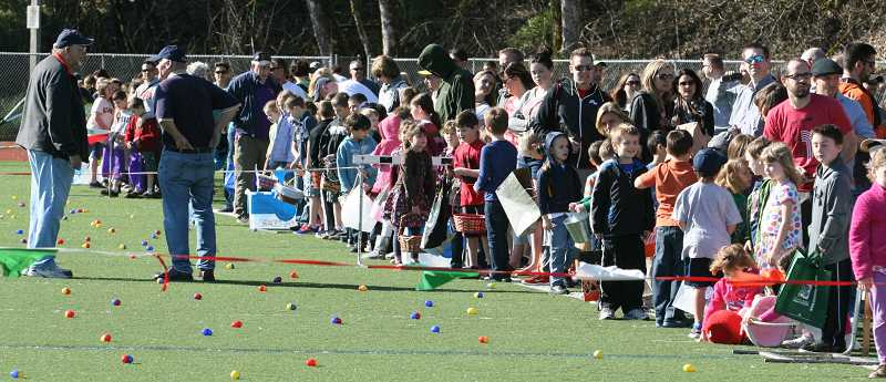 by: J. BRIAN MONIHAN - Eager egg hunters line the entire length of the football field at West Linn High School on Saturday. The hunt, sponsored by both the West Linn Lions Club and the West Linn Riverview Lions Club, included 5,000 eggs stuffed with candy and a few special prizes. This was the 59th annual egg hunt sponsored by the clubs.