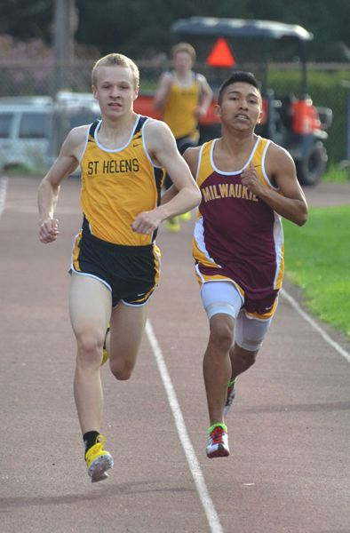 by: JOHN BREWINGTON - St. Helens Bryan Strang pulls in front of Milwaukie's Chris Spanovich during the 800 meter run on Wednesday. Spanovich tried to block Strang from passing but he slipped in front.