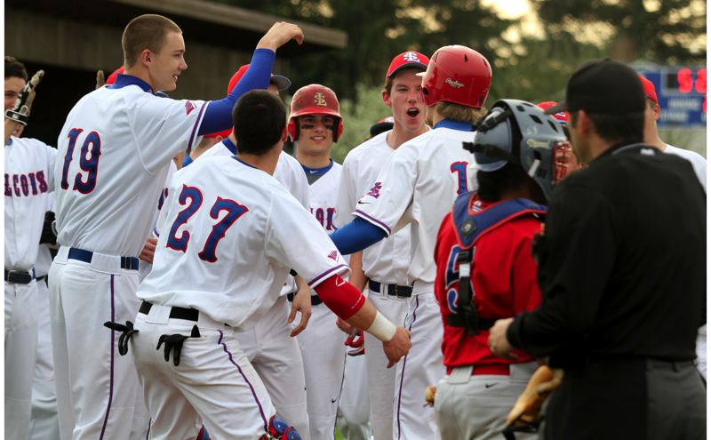 by: JONATHAN HOUSE - La Salle senior Sam Eichhorn is greeted at the plate by teammates after hitting a home run in last weeks 4-2 win over Madras. The Falcons had three home runs in the game.