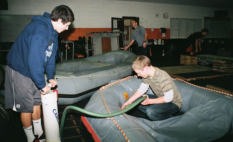 by: JOHN DENNY - Gladstone football players (left) Austin Galvin and Eli Hubbard were busy last Friday, pumping up and checking the condition of rafts scheduled for sale at Gladstone High School on Saturday, April 20.