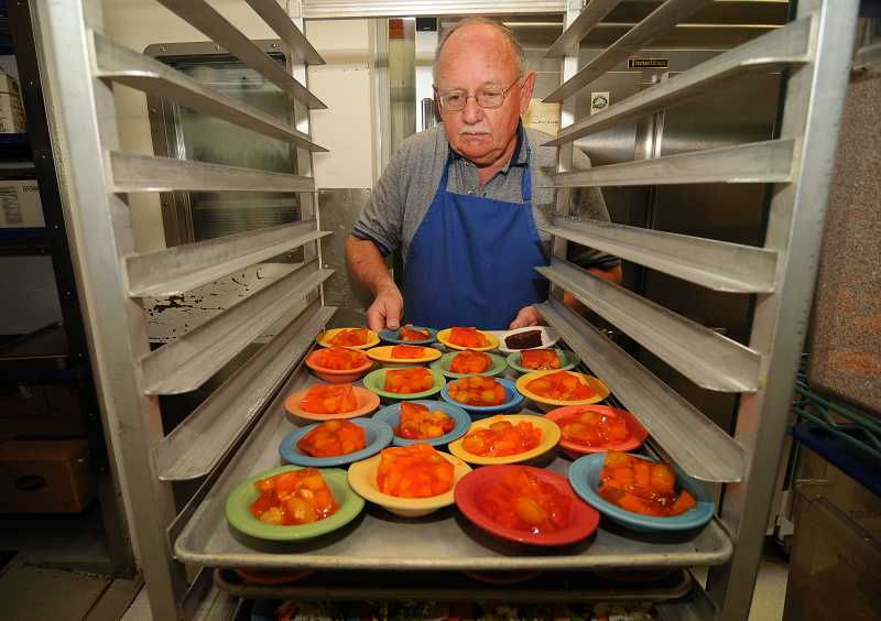 by: REVIEW PHOTO: VERN UYETAKE - John Fowlks prepares meals for patrons of the meals program at the Lake Oswego Adult Community Center.