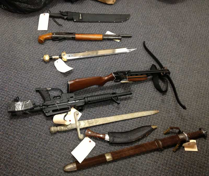 by: WEST LINN POLICE - A variety of weapons, including these knives, swords and guns, were removed from the residence during a police search.