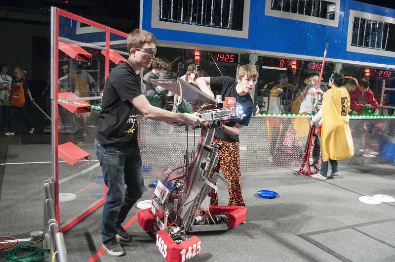 by: PAMPLIN MEDIA GROUP: JOSH KULLA - Team 1425 members hustle their robot onto the field of play earlier this spring at the Portland Regional at Memorial Coliseum.