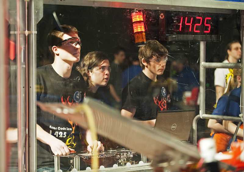 by: PAMPLIN MEDIA GROUP: JOSH KULLA - Team 1425 drive team members operate their robot during a heat last month at the Portland Regional at Memorial Coliseum.