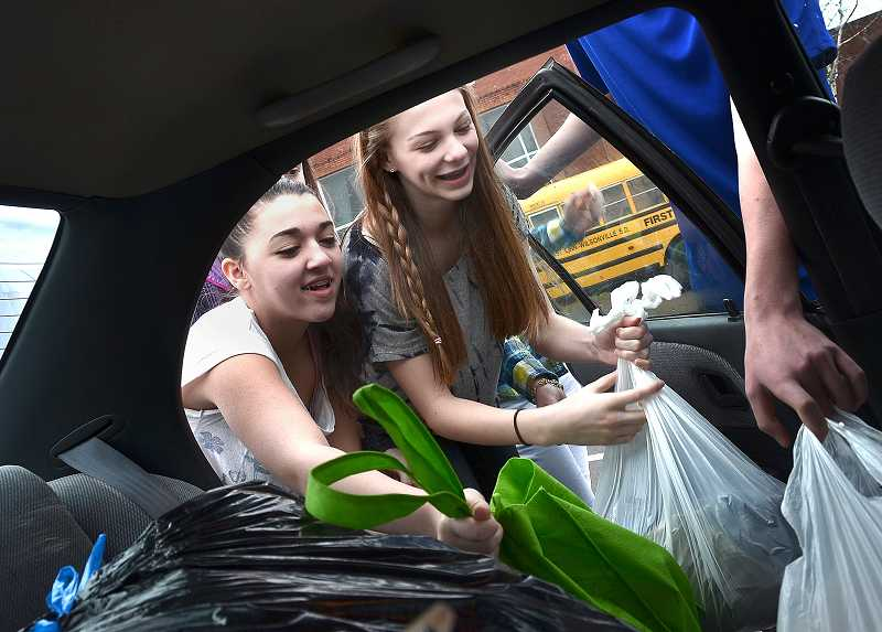 by: TIDINGS FILE PHOTO: VERN UYETAKE - Students collected donations being dropped off at Athey Creek Middle School during last year's garage sale drive.