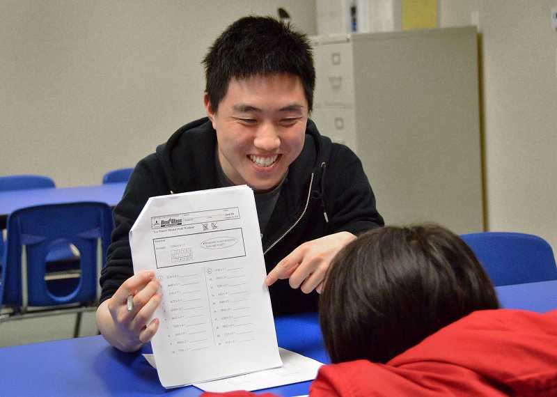by: REVIEW PHOTO: VERN UYETAKE - VERN UYETAKE Math instructor Ryan Hsu works with a pupil.