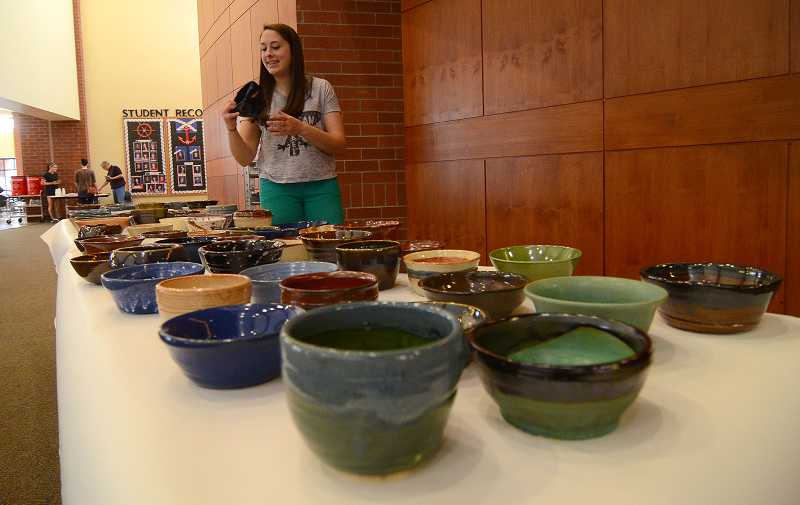 by: REVIEW PHOTO: VERN UYETAKE - LOHS junior Allison Kantor examines some of the bowls that she and her classmates made for the event.
