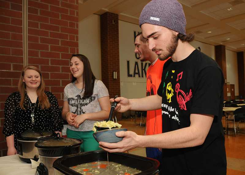 by: REVIEW PHOTO: VERN UYETAKE - LOHS junior Will Bryan dishes up soup at the event.