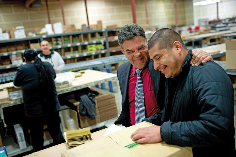 by: TRIBUNE PHOTO: CHRISTOPHER ONSTOTT - David Torres here with Raul Vasquez, insists his many Latino employees refrain from speaking or reading in Spanish while on the job. The goal, he says is for them to be fluent in English.
