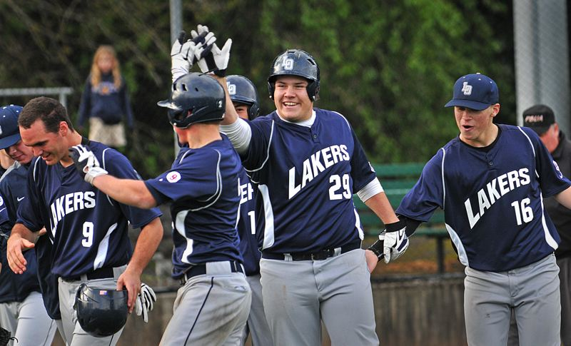by: VERN UYETAKE - Lake Oswego players celebrate following Reid Penney (No. 29)'s grand slam in the fourth inning of the Lakers' win over Lakeridge.