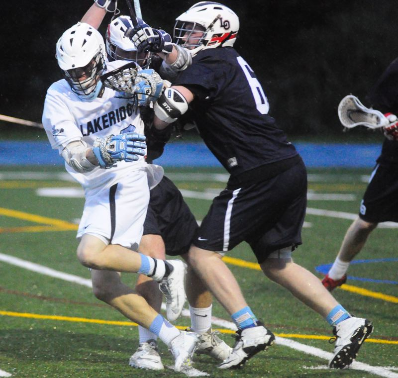by: MATTHEW SHERMAN - Lakeridge's John Finegan absorbs a hit from a pair of Lakers in the Pacers' Civil War victory on Friday.