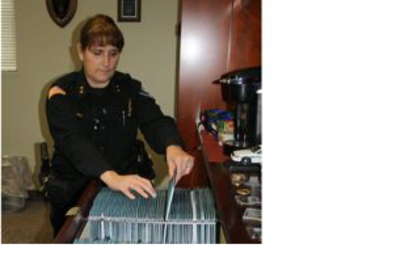 by: POST PHOTO: JIM HART - Sandy Police Chief Kim Yamashita inspects one of 120 file folders, each with evidence to prove the department meets all 120 high standards to be considered for the prestigious status as an accredited police agency. POST PHOTO:  JIM HART