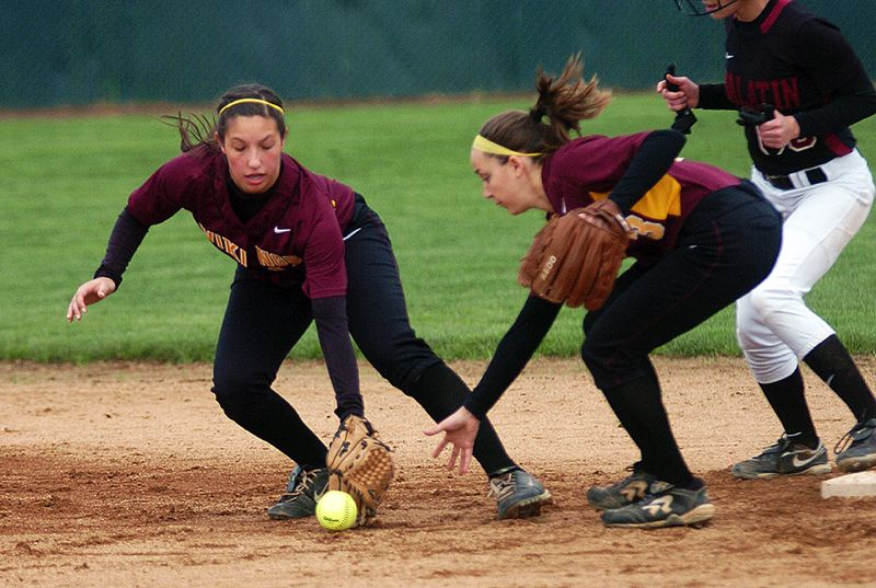 by: PAMPLIN MEDIA GROUP PHOTO: DAN BROOD - Forest Grove sophomore shortstop Sarah Hess (left) and sophomore second baseman Emily Peters both reach for a ground ball during Monday's Pacific Conference softball opener against Tualatin. The Lady Vikings lost the game 2-0.