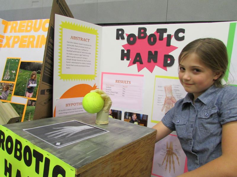 by: SPOTLIGHT PHOTO: ROBIN JOHNSON - Kenna Remmers's robotic hand could grip a football and softball, but couldn't quite grab a pencil or make a peace sign.