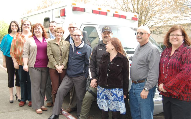 by: PHOTO BY: RAYMOND RENDLEMAN - Board members of Oregon Impact gather to celebrate American Medical Response's donation of an ambulance to educate teens on the dangers of distracted driving.