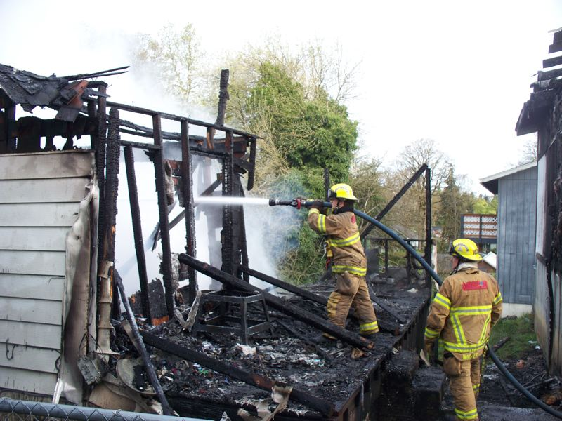 by: SUBMITTED PHOTO - Firefighters bring a blaze at a South Fourth Street residence in St. Helens under control April 12.