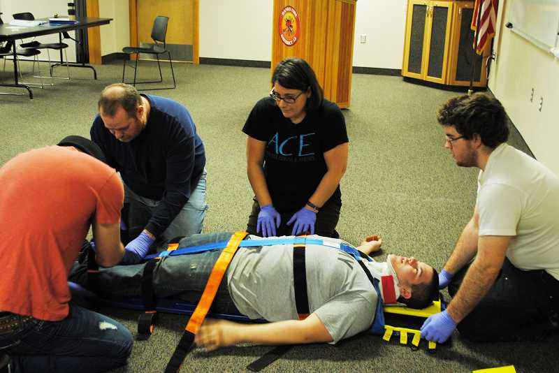 by: NEWS-TIMES PHOTO: STEPHANIE HAUGEN - Christy Greagor completed weeks of emergency medical responder training this year, which included strapping patients on a backboard.