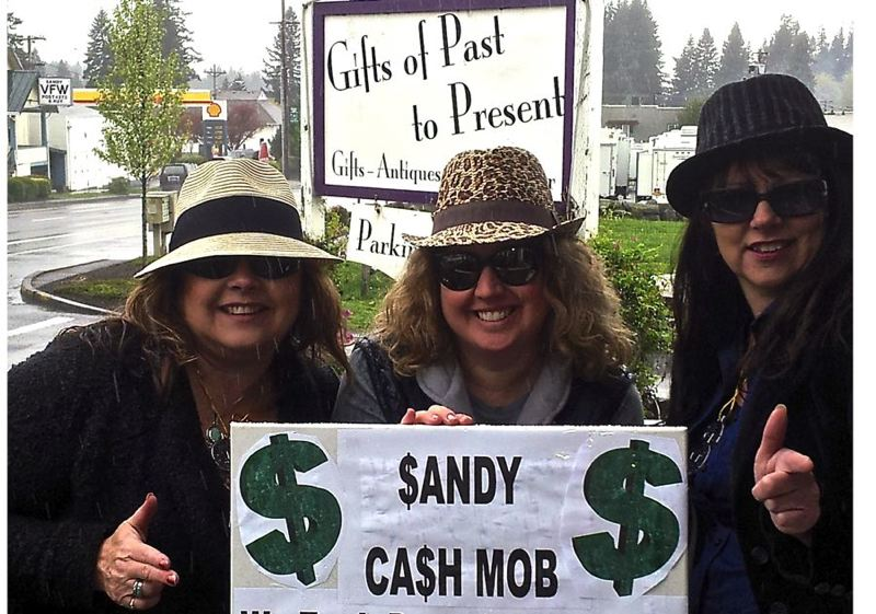 by: CONTRIBUTED PHOTO - Acting like a real mob is a portion of the large cash mob that will descend on Gifts of Past to Present at 11 a.m. Saturday. Standing outside the business, from left, are Lisa Foster, Lacy Renard and Debbie Grimes. CONTRIBUTED PHOTO