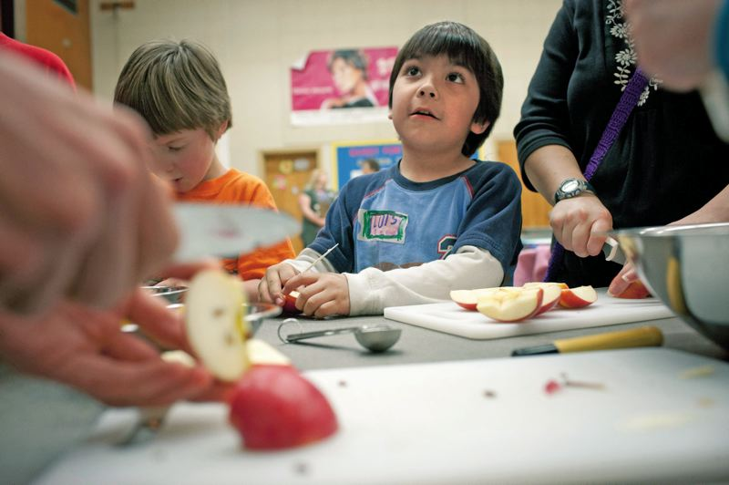 by: PAMPLIN MEDIA GROUP: CHRISTOPHER ONSTOTT - Horacio Anderson, 6, gets tips on how to chop apples while helping prepare an apple cinnamon dish at Zenger Farms cooking class at West Powellhurst Elementary School in Southeast Portland.