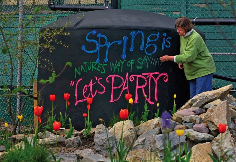 by: PAMPLIN MEDIA GROUP FILE PHOTO: L.E. BASKOW - Jody Foster, da Vinci Middle School teacher, chalks out a message on a water cistern prior to an Earth Day celebration.
